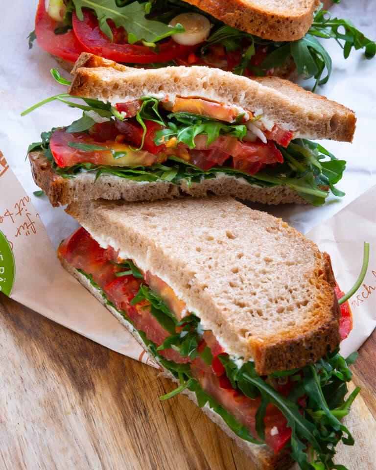 3 Brote mit Frischkäse, Rucola und Tomaten belegt und zusammengeklappt