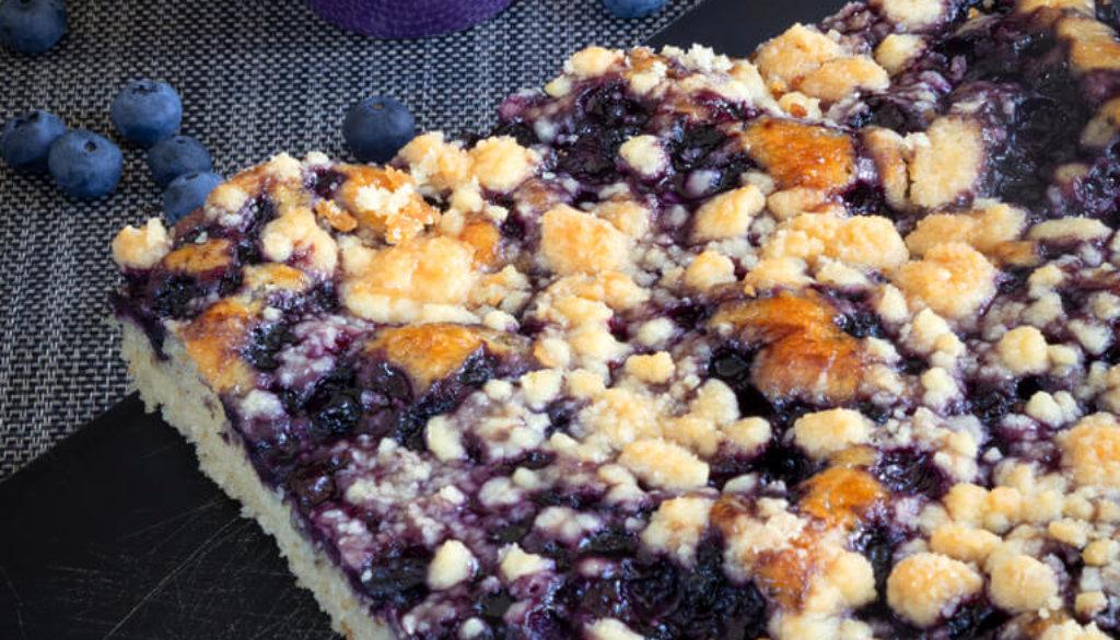 Dinkel-Heidelbeer-Kuchen auf Brett und Heidelbeeren in Schale