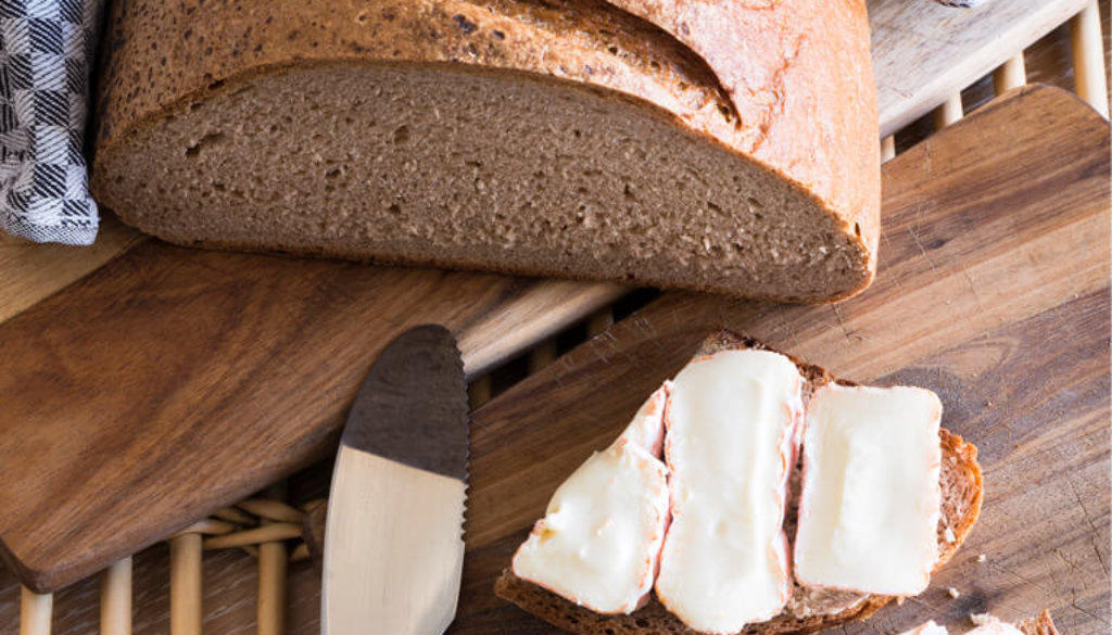 Brot angeschnitten und zum Teil belegt. Mit Handtuch