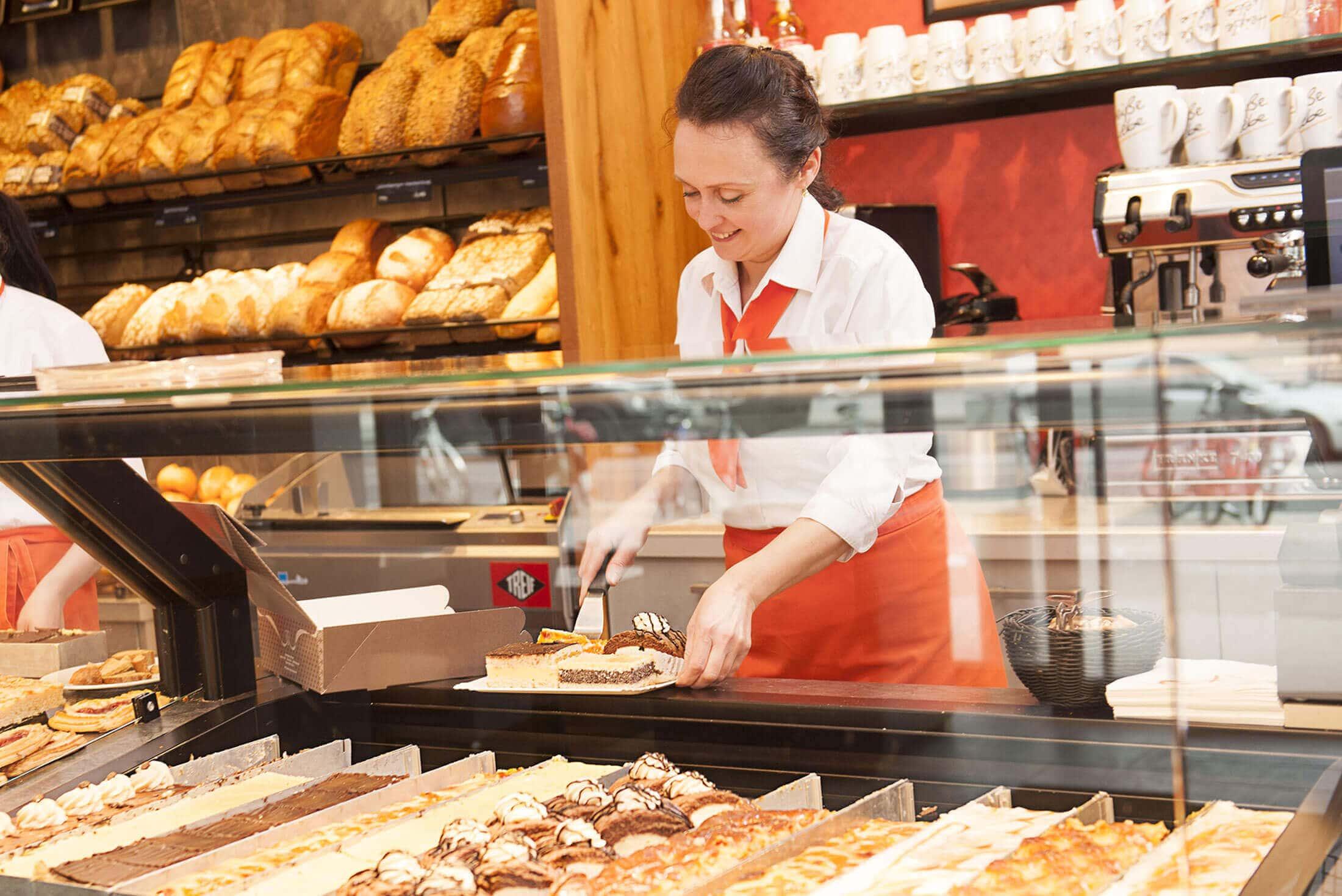 Verkäferin stellt Kuchenstücke zusammen