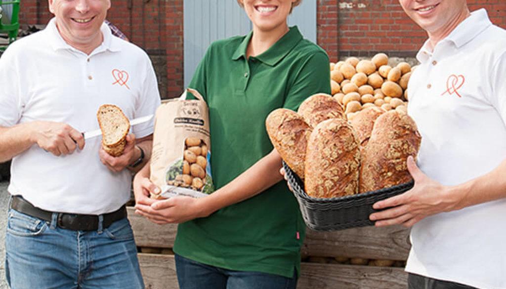 Drei Personen mit Brot und Kartoffeln in den Händen