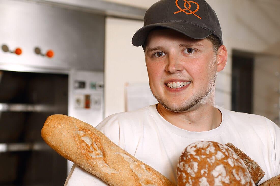 Auszubildender Bäcker mit Baguettestange und Brot in der Hand