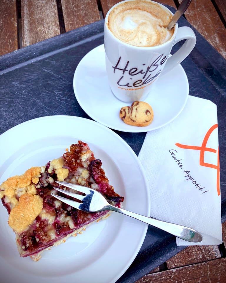 Stück Zwetschenkuchen auf Teller, ein Pot Kaffee mit Keks