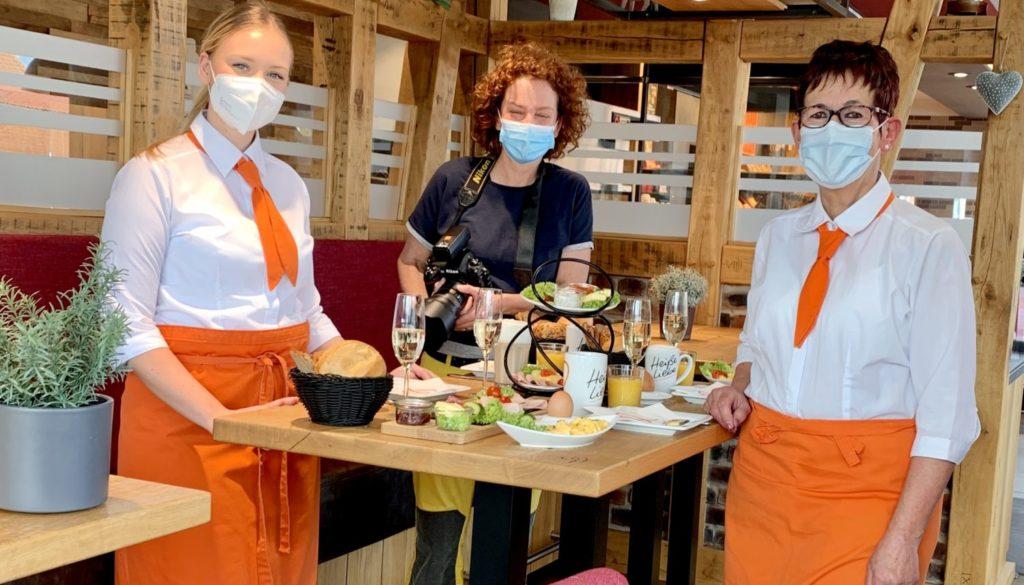 Fotografin mit zwei Verkäuferinnen hinter gedecktem Frühstückstisch